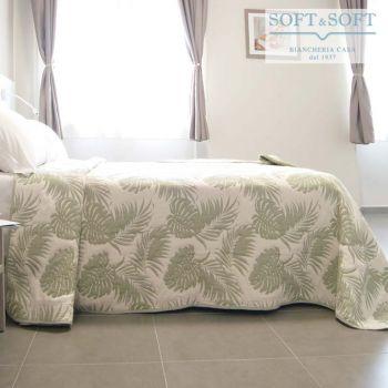 copriletto estivo realizzato con un tessuto jacquard leggermente imbottito, ha due diritti, da un lato è a fondo bianco con foglie di palma verde salvia chiaro, dall'altro è a fondo verde chiaro con foglie bianche