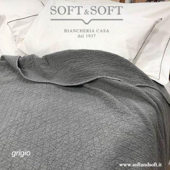 Copriletto di colore grigio medio effetto stone washed, trapuntato con una trapuntatura fitta e morbida, il perimetro è orlato e forma una ampia smerlatura