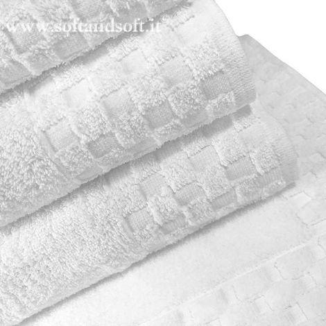asciugamano in spugna di cotone colore bianco, con bordo alto dove il tessuto dell'asciugamano si trasforma in un disegno a quadretti bianchi, finitura studiata apposta in modo che il bordo dell'asciugamano non stringa